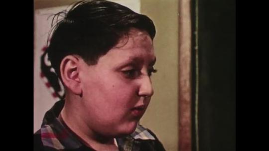 UNITED STATES: 1950s: boy looks sad in classroom. Boys argue.