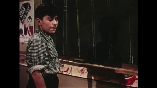 UNITED STATES: 1950s: boy paints with imaginary brush. Boys talk