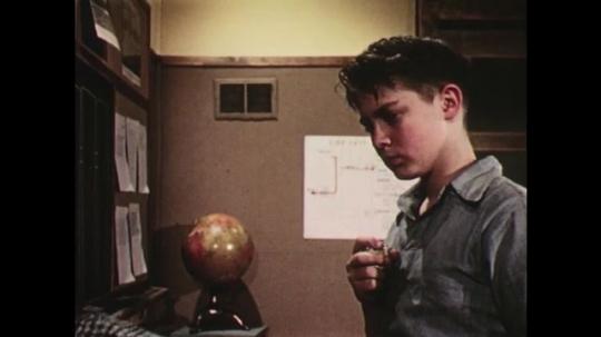 UNITED STATES: 1950s: boy paints with imaginary brush. Boys talk. Boy eats imaginary apple
