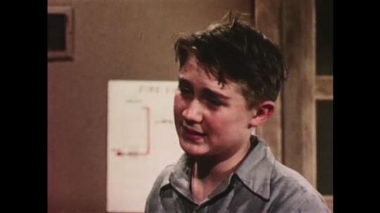 UNITED STATES: 1950s: boy speaks to classmate. Boy leans on blackboard. Boy smiles