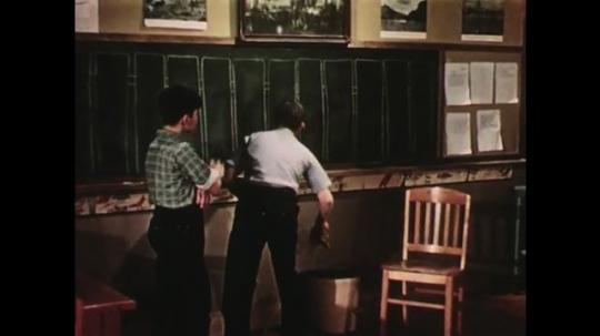 UNITED STATES: 1950s: boy paints with brush. Boy eats apple, Boys make friends