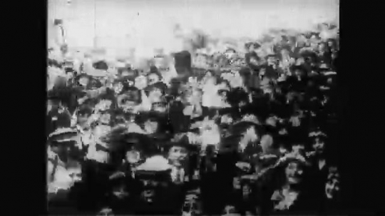 UNITED STATES: 1910s: people cheer and wave as war ends. Soldiers march in street. View across water to city