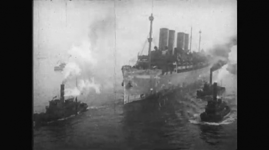 UNITED STATES: 1910s: ships carry soldiers home after war. Soldiers cheer and wave from ship