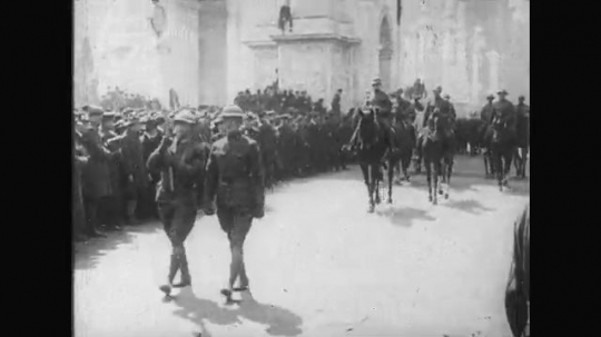 UNITED STATES: 1910s: soldiers on horseback ride through street. Soldiers march through street, Crowds watch soldiers.