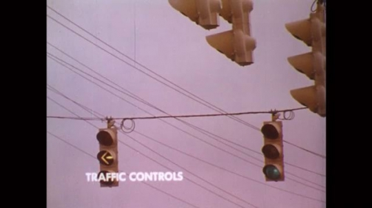 UNITED STATES: 1980s: Traffic controls and traffic lights. Lights change red to green.