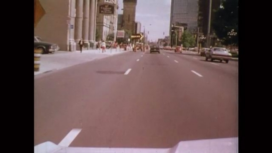 UNITED STATES: 1980s: view of road in city through windshield. Road works along road side