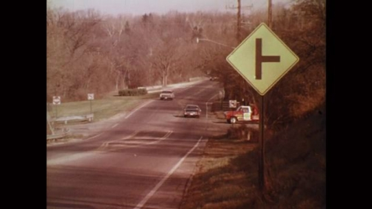 UNITED STATES: 1980s: cars drive along road. Sign on side of road. Vehicle pulls onto road. Close up of sign. View through windshield