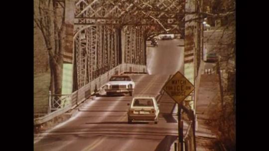 UNITED STATES: 1980s: traffic drives across bridge. Ice on bridge warning sign. Motorbike drives over bridge