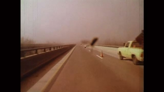 UNITED STATES: 1980s: large fly on windscreen. View along motorway road. Car drives towards fog. View of cyclist on road.