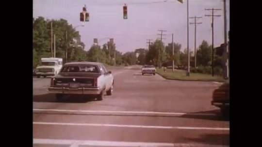 UNITED STATES: 1980s: cars drive along road. Parked car hazard. Car drives behind slow truck