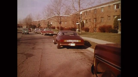 UNITED STATES: 1980s: cars parked outside buildings on street. Arrow points to driver of parked car. Arrow points to indicator on car.