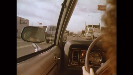 UNITED STATES: 1980s: rear view of driver and hands on steering wheel