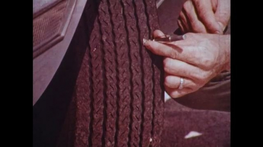 UNITED STATES: 1950s: tyres checked for depth of tread and maximum pressure. Close up of pressure information on tyre. View through car wipers in rain