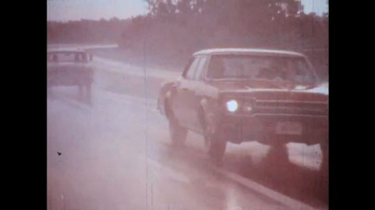 UNITED STATES: 1950s: cars on highway in rain.