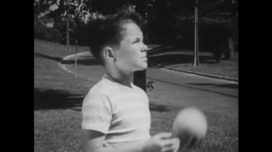 UNITED STATES: 1940s: boy throws ball in air. Boys talk together. Boy puts on cap.
