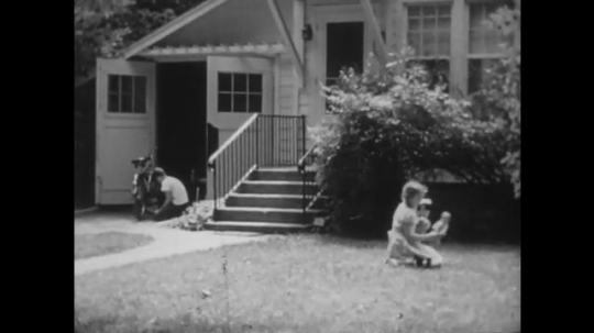 UNITED STATES: 1940s: girl plays with dolls in garden. Boys walk on footpath.