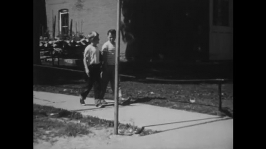 UNITED STATES: 1940s: boys walk together on path. Boys look for traffic on road.