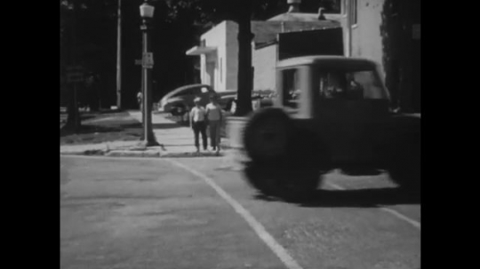 UNITED STATES: 1940s: car drives on road. Boys cross road. Boys walk together. Boy holds ball. Lady carries groceries