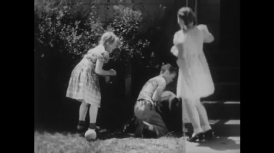 UNITED STATES: 1940s: boy gives puppy to girls. Boy crosses road. Boy eats fruit