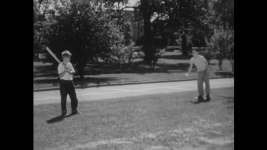 UNITED STATES: 1940s: boy throws ball. Boy practices baseball swing.