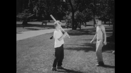 UNITED STATES: 1940s: boy helps friend with baseball skills in park. Boy throws ball. Boy swings bat