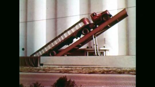 1950s: Truck lifted on ramp, tilt up grain silos. Combine drives through field. Combine harvesting wheat.