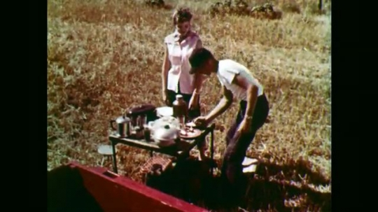 1950s: Boy and girl eat at table in wheat field, boy runs. Man walks through field. Boy starts combine. Combine drives through field.