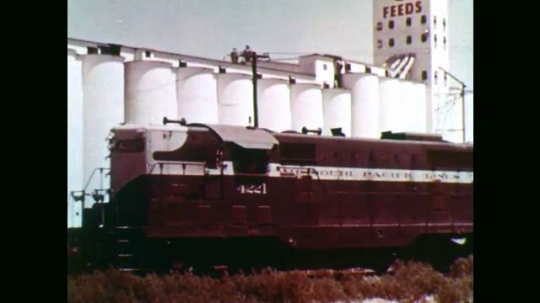 1950s: Train drives past grain silos. High angle view of train. Man in field, looks at hand. Wheat kernels in hand.