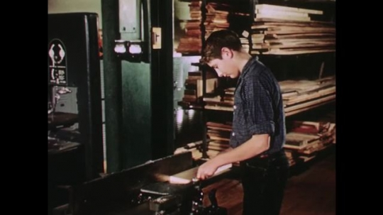 UNITED STATES: 1950s: boy cuts wood on machine.
