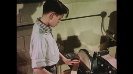 UNITED STATES: 1950s: boy uses machine to curve end of wood