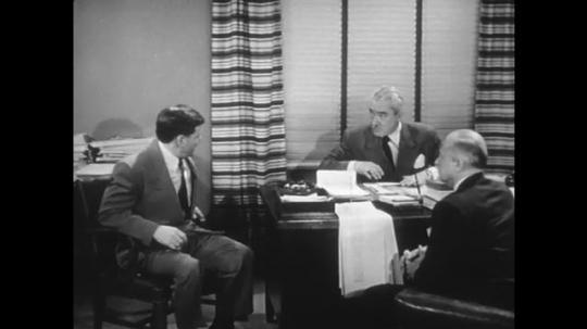 1950s: Men talking in office, man picks up board. Man looks at drawing.