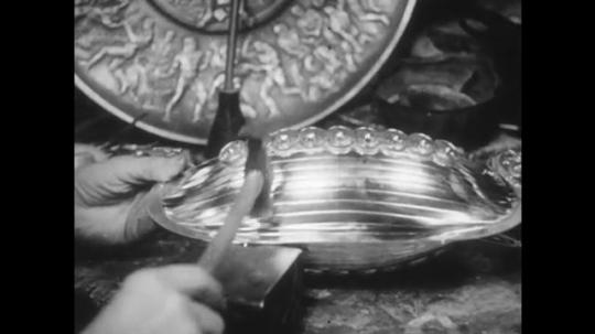 1950s: Hands hammer metal object. Men talking in office. Men in factory. Man adjusts equipment.