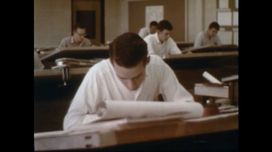 1960s: man writes at architect desk in office with men. man looks around.