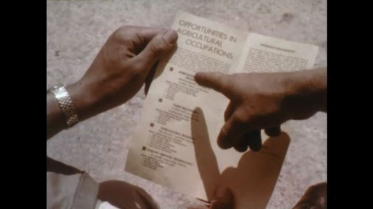 1960s: hands hold brochure for opportunities in agricultural occupations. hand points at brochure. agriculture equipment technolgy in brochure. man talks.