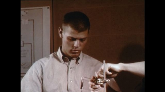 1960s: man looks at chemistry glassware while hand tightens test tube. man looks down. men adjust electronic equipment and slide ruler. man turns knob on electronic device.