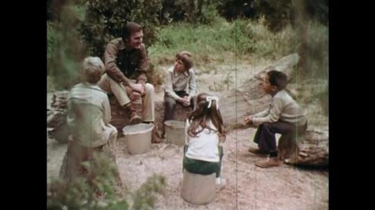1970s: UNITED STATES: children in woods listen to man speak. Close up of boy's face. Cigarette on floor.