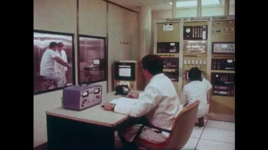 1980s: People working in lab. Man rides bike in lab, man watches. Hands look at electrical readout, view of gauge, zoom out. Man rides bike, other man looks at equipment.