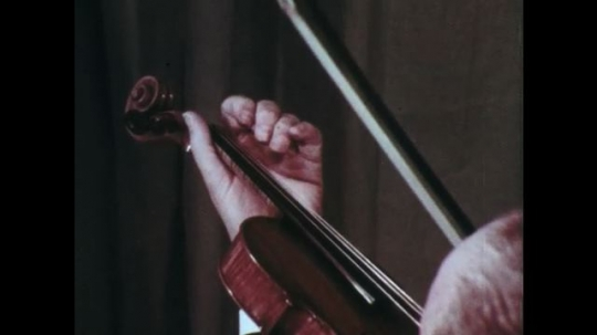 Man with suit plays violin in room with curtained background.