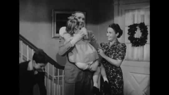 UNITED STATES: 1940s: man carries girl in house. Lady hugs girl. Man talks to family.
