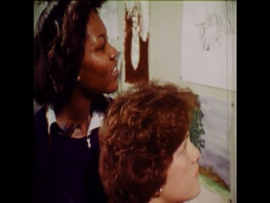 UNITED STATES 1970s: Two young women look at paintings on a wall, a professional painter paints over a graffiti covered wall.